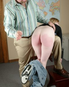 Een studente die over de knie ligt met haar spijkerbroek op haar enkel en op haar billen krijgt.