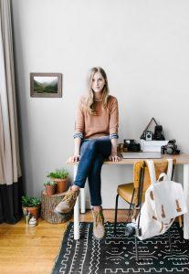 Een meisje zit op een tafel in een woonkamer en kijkt je aan.