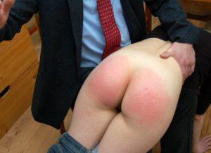 Een studente die over de knie ligt en op haar blote billen krijgt.