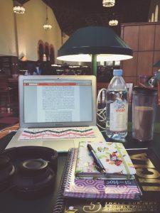 De werkplek van een studente met een laptop, een agenda, boeken en een fles water.