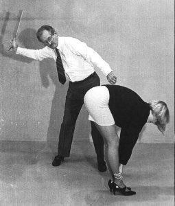 Een foto uit het verleden, waarbij een voorover gebogen studente in een rok met de paddle op haar billen krijgt.
