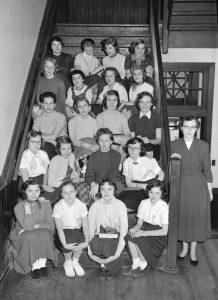 Studentes in een Amerikaans studentenhuis uit de vijftiger jaren, met hun 'huismoeder'.