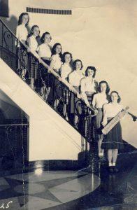Een trap in een sorority-huis, waarbij de bewoonsters laten zien met welke paddle ze op hun billen krijgen.