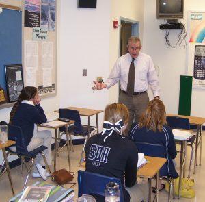 Een docent op een Amerikaanse High School die les geeft aan een aantal studentes.