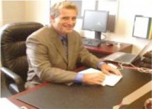 Een foto Principal Durham van de oude website van de school. Hij geeft oudere studenten die regels overtreden altijd een stevig pak op hun billen. Voor de jongens gebruikt hij een wat zwaardere paddle dan voor de meiden. De paddle waarmee de meiden op hun billen krijgen ligt klaar op het bureau om direct te gebruiken.